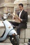 Giornale della lettura di Sitting By Scooter dell'uomo d'affari fotografie stock libere da diritti