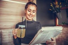 Giornale della lettura della giovane donna e limonata bevente Fotografia Stock Libera da Diritti