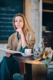 Giornale di pensiero del caffè di dubbio della giovane donna della tavola del ristorante Fotografie Stock Libere da Diritti