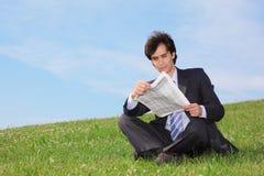Giornale di seduta e della lettura dell'uomo d'affari Fotografie Stock Libere da Diritti