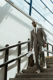 Giornale e cartella d'uso della tenuta del vestito dell'uomo d'affari afroamericano mentre camminando immagine stock libera da diritti
