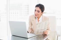 Giornale felice della lettura della donna di affari mentre lavorando al computer portatile Immagine Stock
