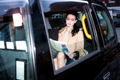 Giornale femminile della lettura del passeggero dentro il taxi Immagini Stock