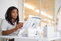 Giornale grazioso della lettura della donna di affari al suo scrittorio Immagine Stock