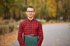 Giornale maschio felice della lettura del responsabile e sorridere fuori nel parco di autunno Concetto dell'uomo d'affari e del m immagine stock libera da diritti