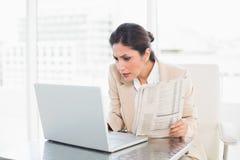 Giornale severo della tenuta della donna di affari mentre lavorando al computer portatile Fotografie Stock Libere da Diritti