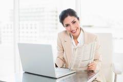 Giornale sorridente della tenuta della donna di affari mentre lavorando al computer portatile Fotografia Stock Libera da Diritti