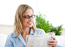 Giornale sveglio della lettura della donna di affari con i vetri Immagini Stock Libere da Diritti