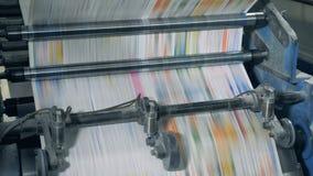 Giornali di stampa nella tipografia Moto rapido di carta colorata attraverso il meccanismo tipografico stock footage