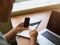 Giornalista maschio che lavora con il telefono delle cellule ed il NET-libro del portatile, sedentesi nello spazio dilavoro fotografie stock libere da diritti