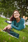Giorno che sogna studente casuale che si trova sull'erba facendo uso della compressa Fotografia Stock