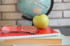 Giorno degli insegnanti del mondo a scuola Natura morta con i libri, globo, Apple, fuoco selettivo di vetro Fotografia Stock Libera da Diritti