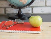Giorno degli insegnanti del mondo a scuola Natura morta con i libri, globo, Apple, fuoco selettivo di vetro Immagine Stock