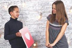Giorno del biglietto di S Giovane ragazzo che dà un'immagine del cuore alla sua amica Fotografia Stock