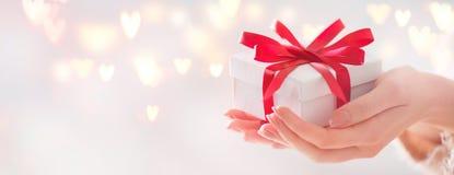 Giorno del `s del biglietto di S Contenitore di regalo della tenuta della donna con l'arco rosso Fotografie Stock