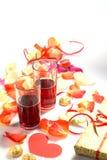 Giorno del `s del biglietto di S Due vetri con vino rosso ed i regali Fotografia Stock