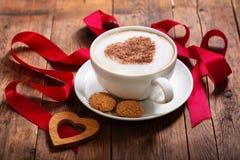 Giorno del `s del biglietto di S Tazza del caffè del cappuccino con cuore su schiuma immagini stock