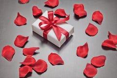 Giorno del ` s del biglietto di S. Valentino presente con i petali di rosa rossa Fotografie Stock