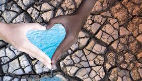 Giorno dell'ambiente La gente si tiene per mano nella forma del cuore, con acqua e suolo asciutto sui precedenti Concetto di cons fotografia stock