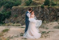 Giorno delle nozze La sposa e lo sposo si abbracciano tenero contro il contesto di fauna selvatica al tramonto fotografie stock