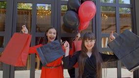 Giorno di acquisto, amici femminili allegri che ondeggiano le borse con i nuovi acquisti dal negozio di modo nella vendita stagio archivi video