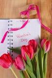 Giorno di biglietti di S. Valentino scritto in taccuino, tulipani freschi e regalo avvolto, decorazione per i biglietti di S. Val Fotografie Stock