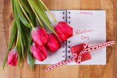 Giorno di biglietti di S. Valentino scritto in taccuino, tulipani freschi e regalo avvolto, decorazione per i biglietti di S. Val Immagine Stock Libera da Diritti