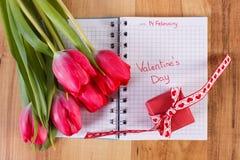 Giorno di biglietti di S. Valentino scritto in taccuino, tulipani freschi e regalo avvolto, decorazione per i biglietti di S. Val Fotografia Stock