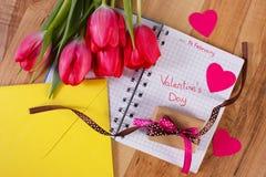 Giorno di biglietti di S. Valentino scritto in taccuino, in tulipani freschi, nella lettera di amore, in regalo e nei cuori, deco Immagini Stock Libere da Diritti