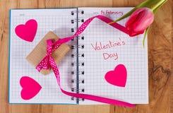Giorno di biglietti di S. Valentino scritto in taccuino, in tulipano fresco, in regalo avvolto e nei cuori, decorazione per i big immagini stock libere da diritti