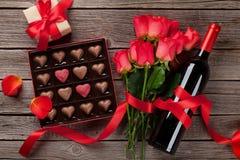 Giorno di biglietti di S. Valentino con le rose rosse, la bottiglia di vino ed il contenitore di cioccolato immagini stock