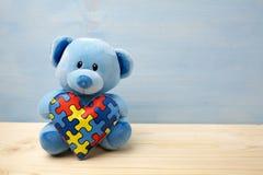 Giorno di consapevolezza di autismo del mondo, concetto con il puzzle della tenuta dell'orsacchiotto o modello del puzzle su cuor immagini stock