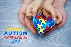 Giorno di consapevolezza di autismo del mondo, puzzle o modello del puzzle su cuore con le mani autistiche del padre e del bambin fotografia stock libera da diritti