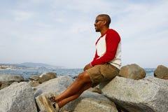 Giorno di estate enjoing sorridente dei giovani pantaloni a vita bassa afroamericani sulla spiaggia fuori della città Fotografie Stock Libere da Diritti