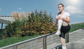 Giorno di estate pieno di sole Giovane donna che fa allungando gli esercizi all'aperto Ragazza che fa riscaldamento sui punti pri Immagine Stock