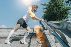 Giorno di estate pieno di sole Giovane donna che fa allungando gli esercizi all'aperto Ragazza che fa riscaldamento sui punti pri Fotografia Stock