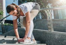 Giorno di estate pieno di sole Giovane donna che fa allungando gli esercizi all'aperto Ragazza che fa riscaldamento sui punti pri Immagini Stock