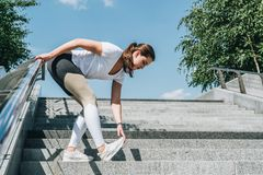 Giorno di estate pieno di sole Giovane donna che fa allungando gli esercizi all'aperto Ragazza che fa riscaldamento sui punti pri Fotografie Stock
