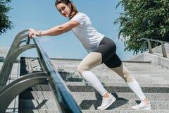 Giorno di estate pieno di sole Giovane donna che fa allungando gli esercizi all'aperto Ragazza che fa riscaldamento sui punti pri Fotografie Stock Libere da Diritti