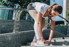 Giorno di estate pieno di sole Giovane donna che fa allungando gli esercizi all'aperto Ragazza che fa riscaldamento sui punti pri Immagini Stock Libere da Diritti