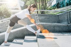 Giorno di estate pieno di sole Giovane donna che fa allungando gli esercizi all'aperto Ragazza che fa riscaldamento sui punti pri Fotografia Stock Libera da Diritti