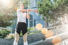 Giorno di estate pieno di sole Giovane donna che fa allungando gli esercizi all'aperto Ragazza che fa riscaldamento sui punti pri Immagine Stock Libera da Diritti