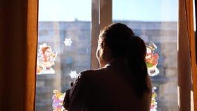 Giorno di inverno freddo La ragazza apre la finestra e inspira l'aria gelida stock footage
