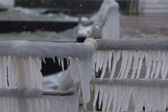 Giorno di inverno sulla spiaggia, ghiaccioli sull'inferriata del metallo della banchina Fotografia Stock Libera da Diritti