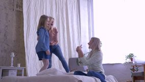 Giorno di madre, ragazze divertenti delle età differenti cantare e divertiresi sul letto per la mamma nella sala a casa nel tempo