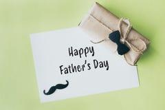 Giorno di padri Pacchetto del regalo avvolto con carta e la corda con una cravatta a farfalla decorativa su fondo verde fotografia stock libera da diritti