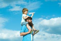 Giorno di padri Sogno del volo Tempo divertente goda Padre e bambino felici della famiglia sul prato con un aquilone di estate so fotografia stock