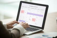 Giorno facendo uso del calendario digitale sul computer portatile, clo di pianificazione della donna di affari immagine stock