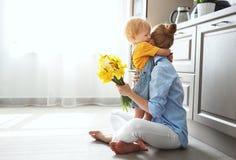 Giorno felice del ` s della madre! il figlio del bambino dà la madre di flowersfor in vacanza Immagine Stock Libera da Diritti