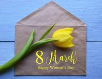Giorno felice del ` s delle donne Busta gialla della carta e del tulipano con testo su fondo di legno blu Immagine Stock Libera da Diritti
